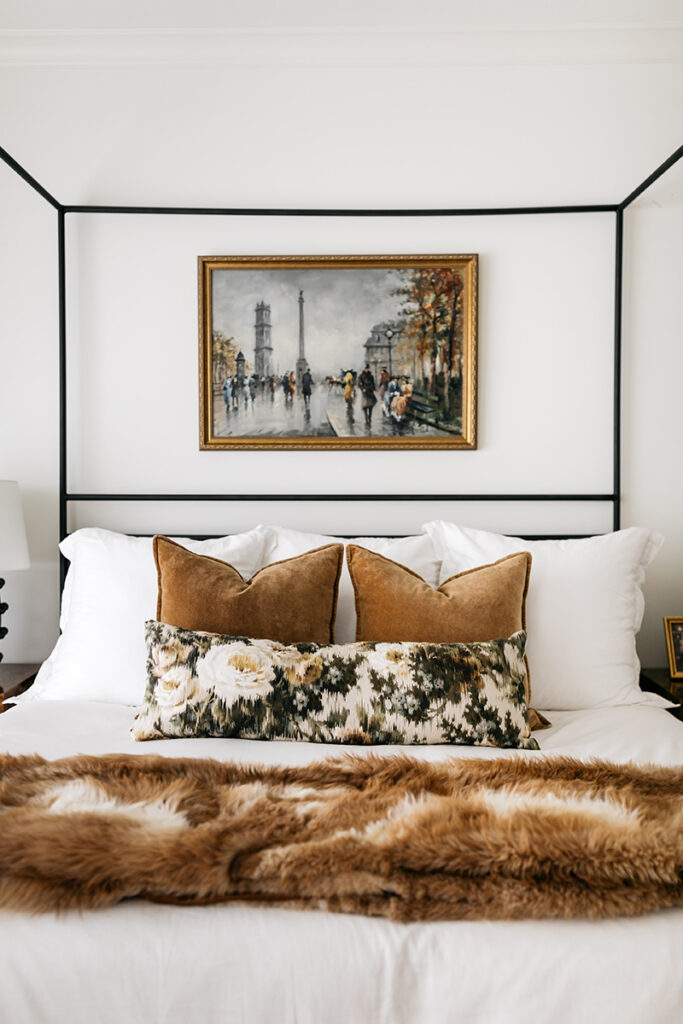 VELVET PILLOWS AND DARK FLORAL ACCENT PILLOW ON WHITE BED